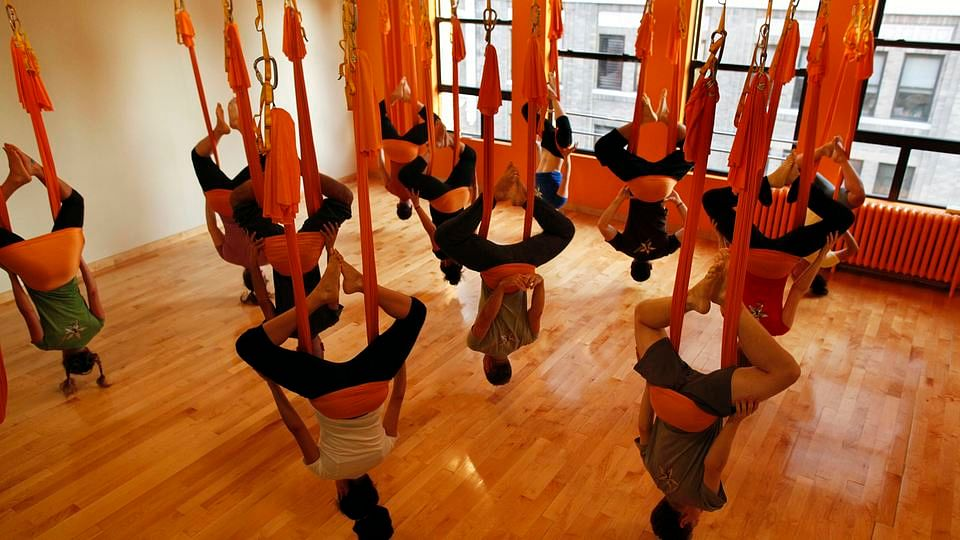 """Students hang upside down in hammocks as they take part in an """"antigravity"""" yoga class."""