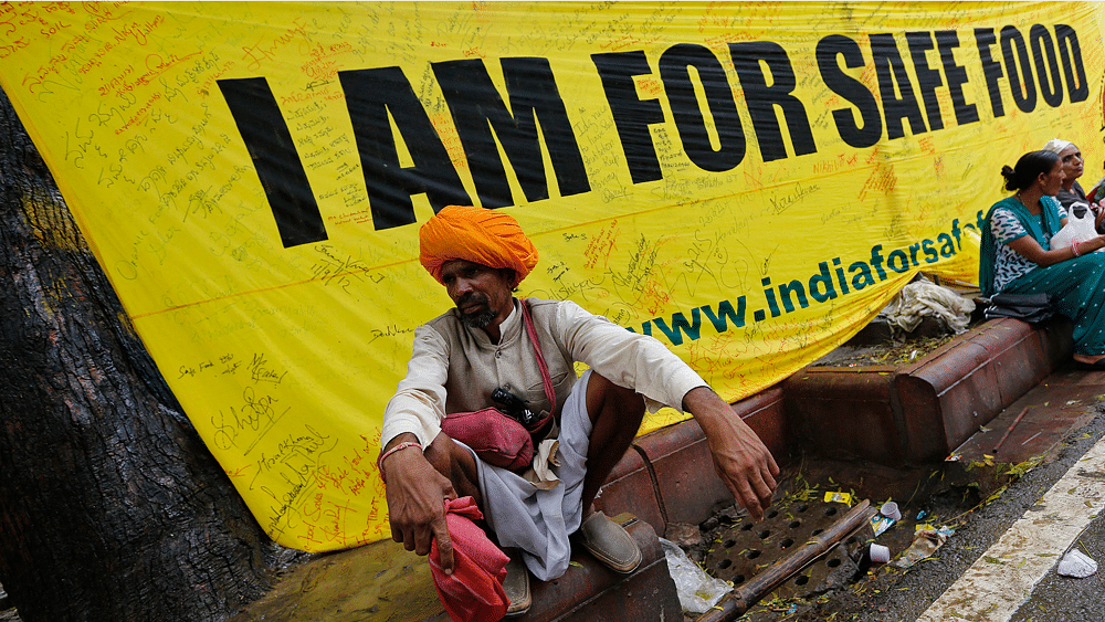 A farmer squats along a footpath near a banner during a day-long protest in New Delhi August 8, 2013. (Photo: Reuters)