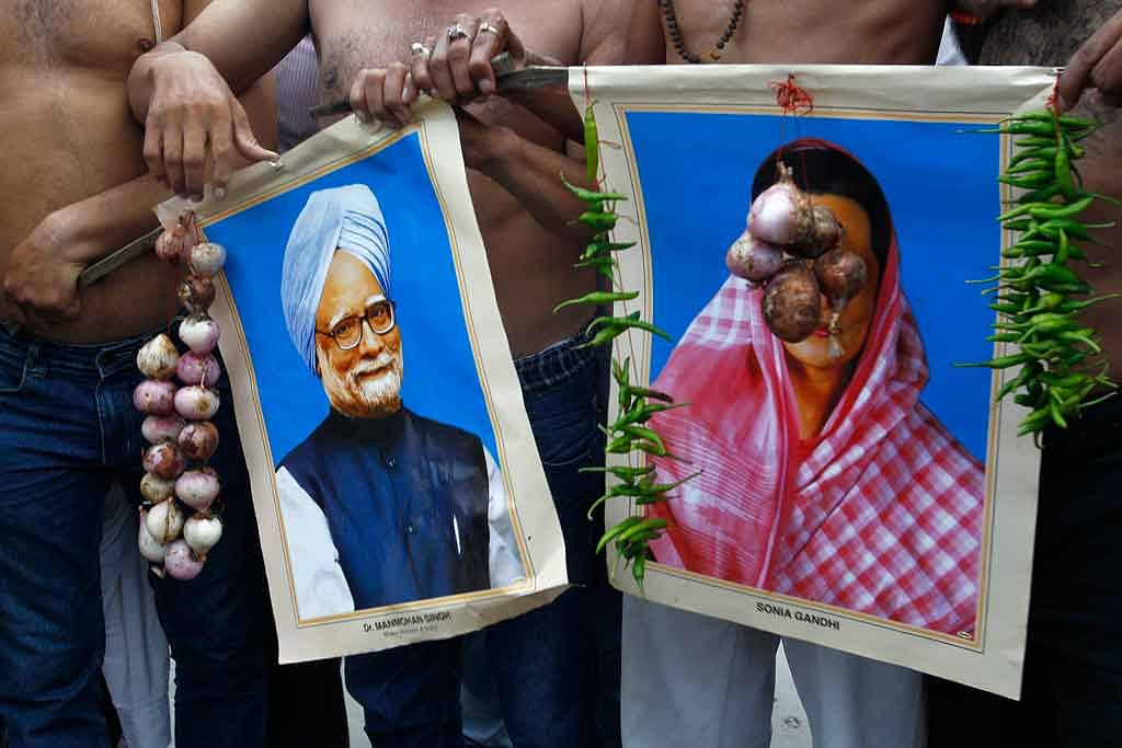 August 14, 2013: Protesters belonging to the BJP hold garlands of onions and green chillies around portraits of Prime Minister Manmohan Singh and Congress President Sonia Gandhi in Allahabad. (Photo: Reuters)