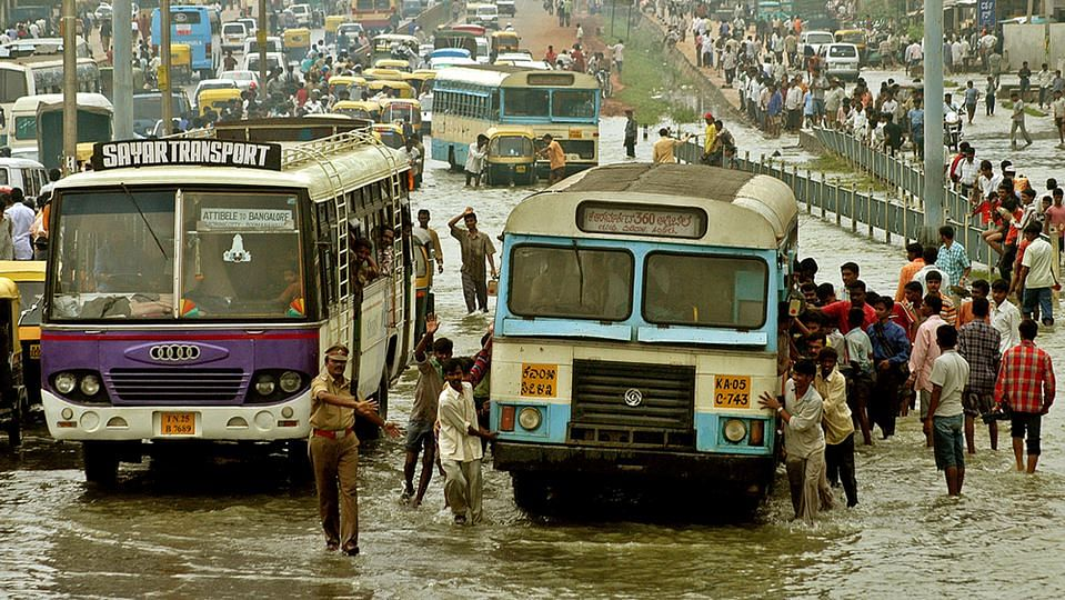 File photo shows people push a bus through a flooded road in Bengaluru.