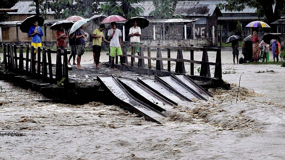 Villagers stand on a half-submerged wooden bridge in the flood hit Baska district, Assam.