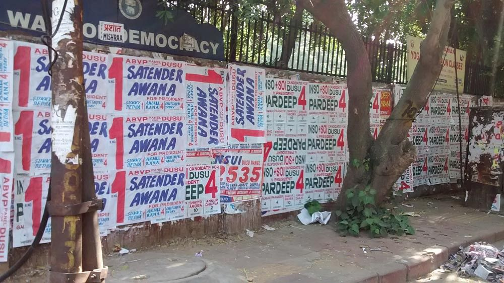 Walls plastered by campaign bills for ABVP and NSUI candidates. (Photo: Neha Yadav/The Quint)