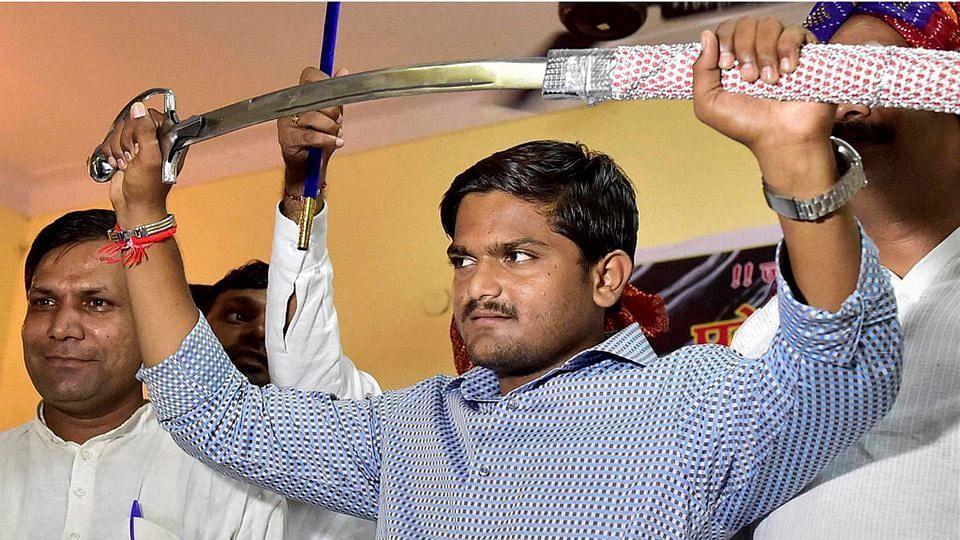Hardik Patel, convener of the Patidar Anamat Andolan Samiti (PAAS), brandishes a sword presented to him at a function organised by Gujjars in New Delhi. (Photo: PTI)