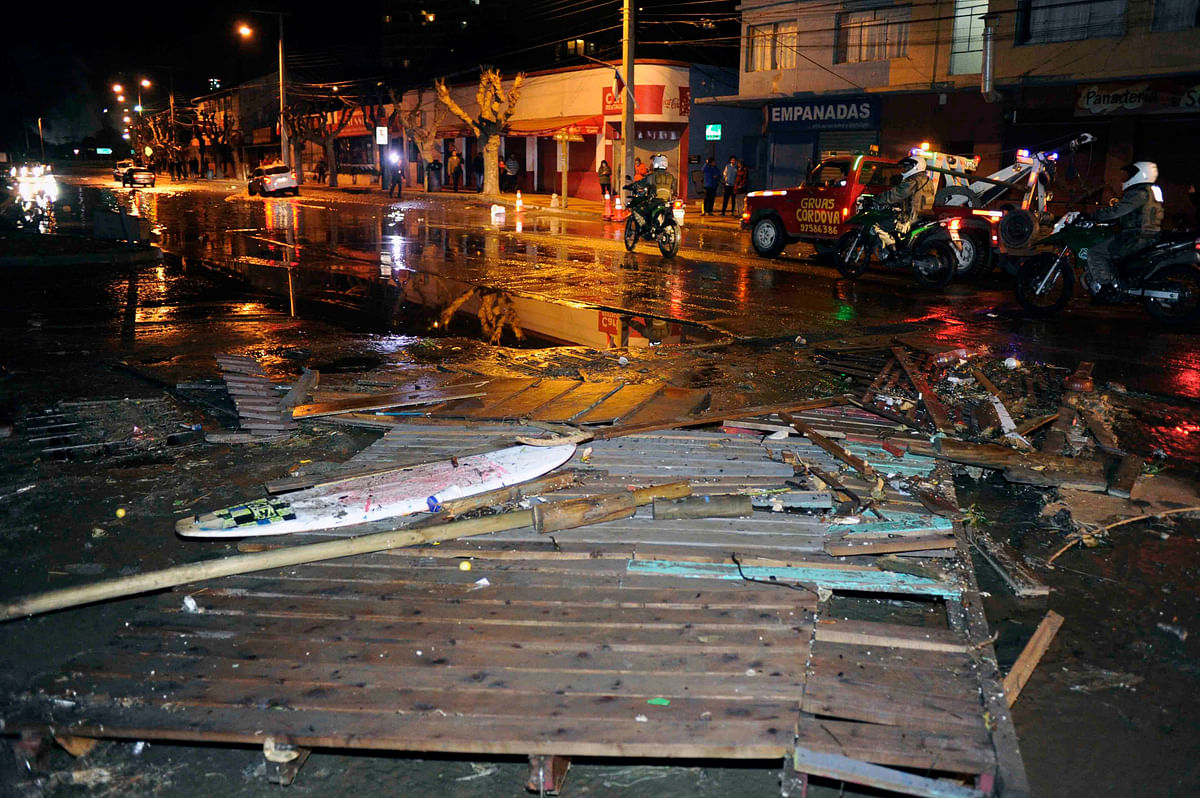 Police patrol a debris strewn street in Valparaiso, Chile, after a tsunami, caused by an earthquake hit the area, Wednesday. (Photo: AP)