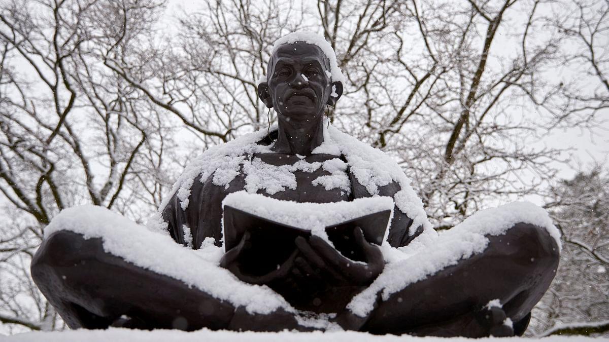 Snow falls on a statue of Mahatma Gandhi on a winter morning in Geneva. (Photo: Reuters)
