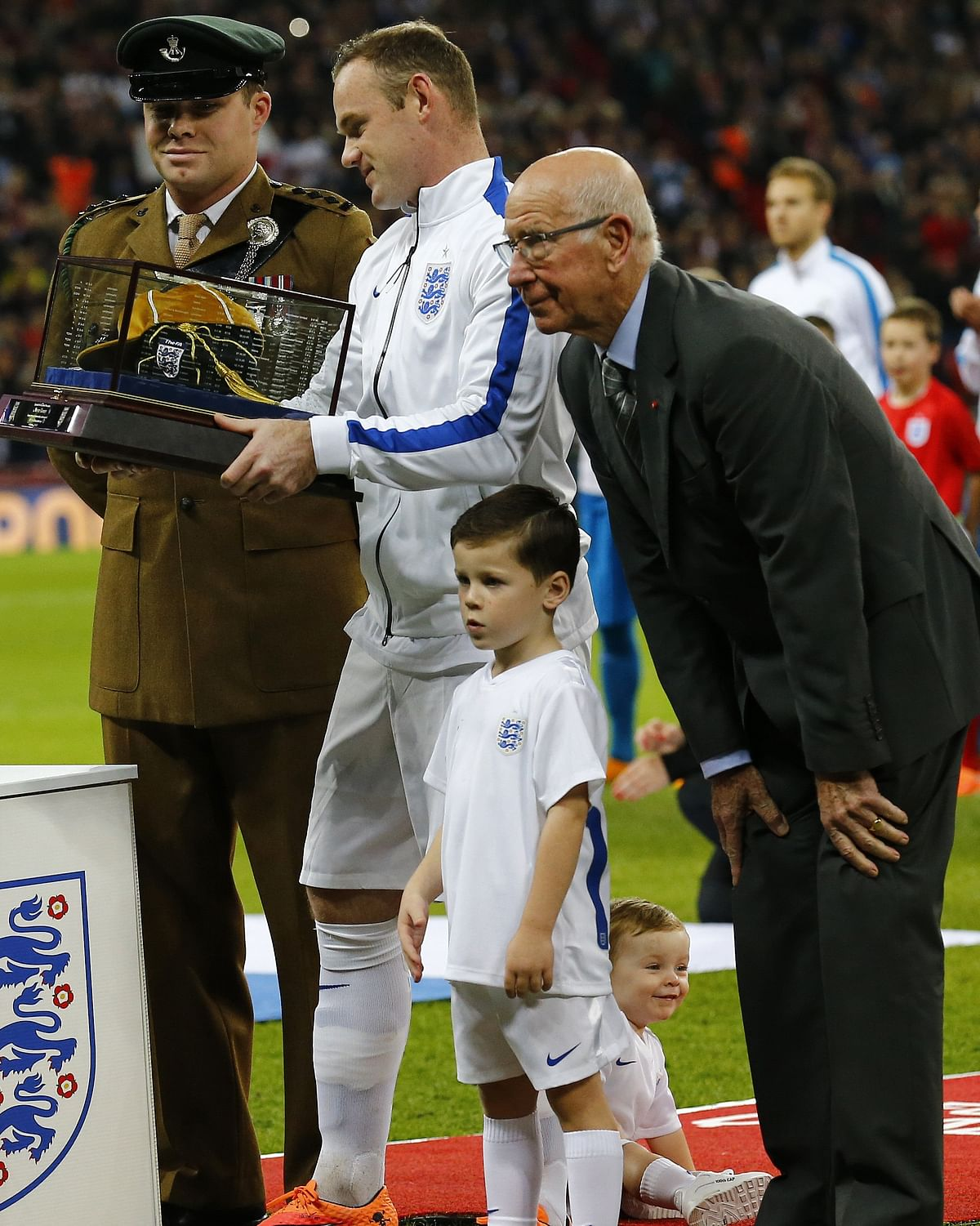 Wayne Rooney receives a golden cap from Bobby Charlton marking his 100th game for England. (Photo: Reuters)