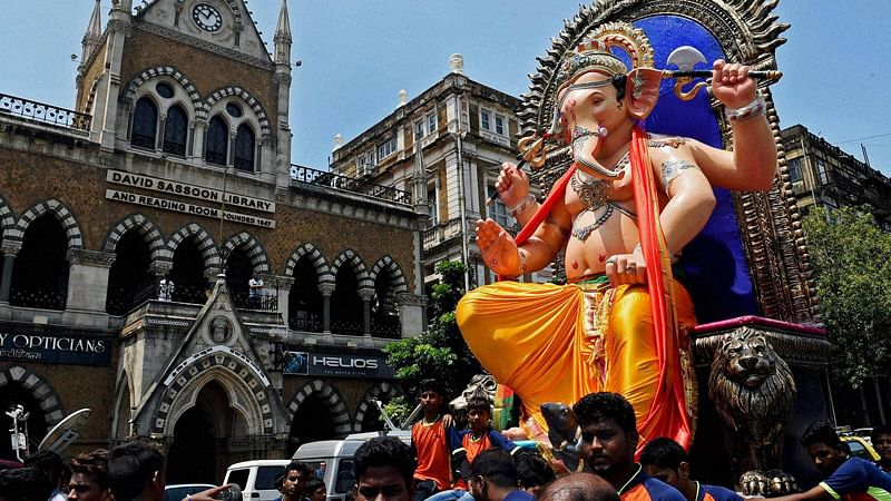 Devotees in Mumbaicarry an idol of Lord Ganesha to a pandal (Photo: PTI)