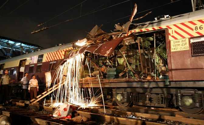 Workers cut a damaged part of the local train compartment hit by the blast. (Photo: Reuters)