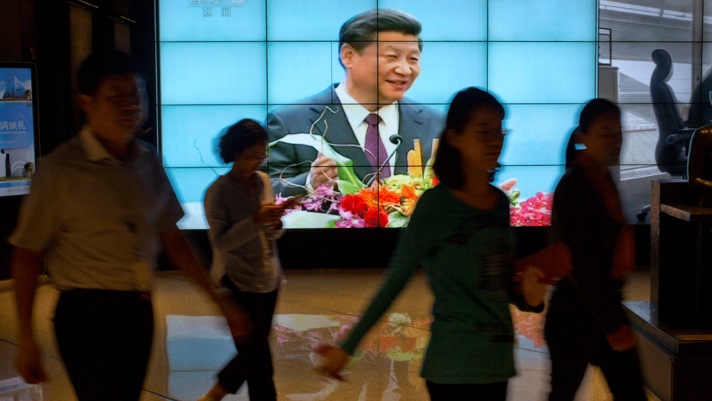 People walk past a large videoscreen showing Chinese President Xi Jinpingduring his trip to the United States from Chinese state broadcaster CCTV in an office building in Beijing, Friday, Sept. 25, 2015.(Photo: AP)