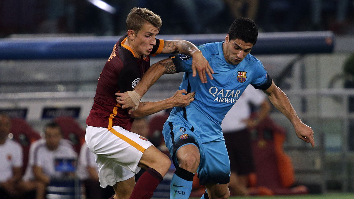 Luis Suarez fights for the ball with AS Roma's Lucas Digneduring their Champions League group match. (Photo: Reuters)