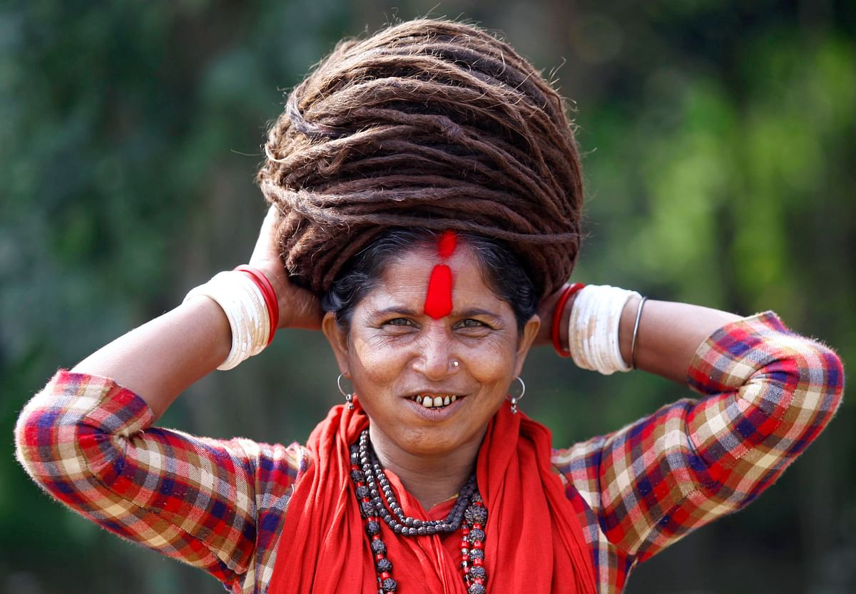 A Hindu ascetic woman smiles as she adjusts her hair after taking a dip in the Ganga river (Photo: Reuters)