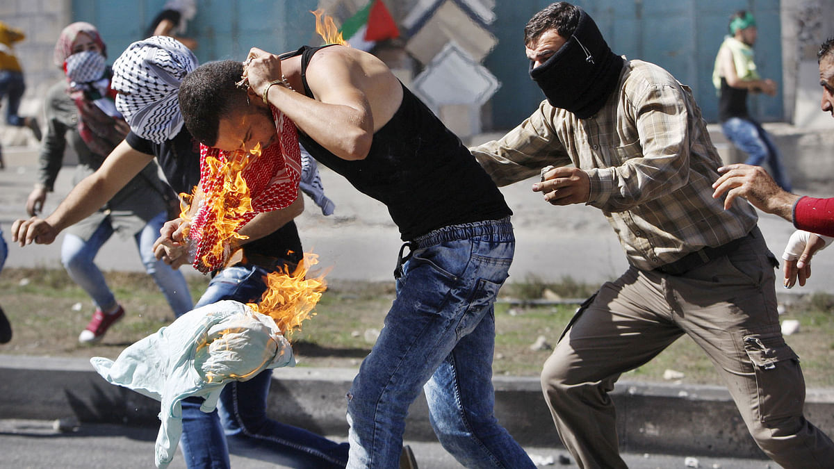 Palestinian protesters put out a fire burning on a compatriot, caused by a molotov cocktail which he was trying to hurl at Israeli troops during clashes in the West Bank city of Hebron. (Photo: Reuters)