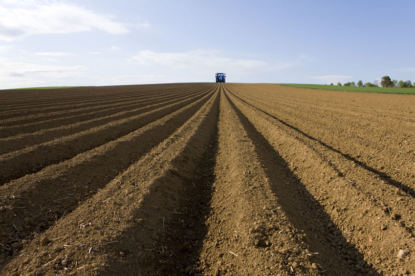 Ploughed field with tractor in distance. (Photo: iStockphoto)