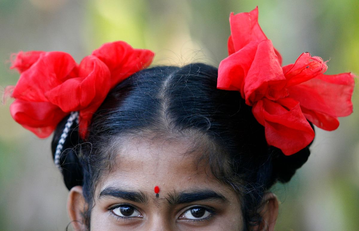 Kamala, an Indian girl wears red ribbons in her hair. (Photo: Reuters)
