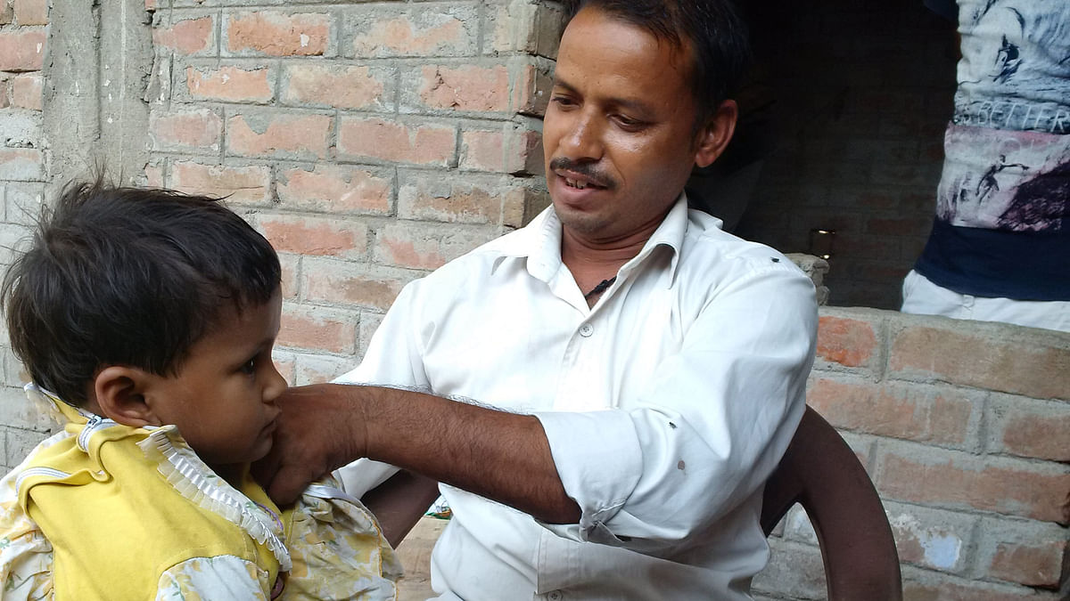 Ram Kumar, a Mahadalit from Mathura hamlet in Checher village, helping his daughter wear a frock. (Photo: <b>The Quint)</b>