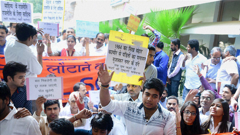A group of people displaying placards during a protest against authors and writers who returned the Sahitya Akademi Awards at Rabindra Bhawan in New Delhi on Friday. (Photo: PTI)