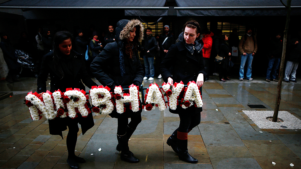 Women carry a floral tribute at an event to mark Nirbhaya's first anniversary outside the Indian High Commission in Central London, December 16, 2013. (Photo: Reuters)