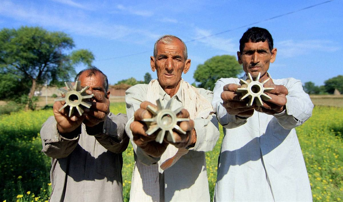 Villagers show parts of mortar shells fired from the Pakistani side of the border, in Bobiya village of Hiranagar sector in Jammu. (Photo: PTI)