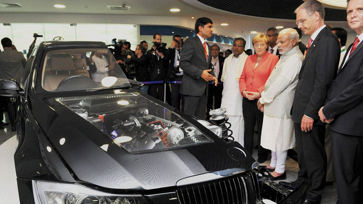 Prime Minister Narendra Modi and German Chancellor Angela Merkel during their visit to Robert Bosch Engineering & Innovation Centre in Bengaluru on Tuesday. (Photo: PTI)