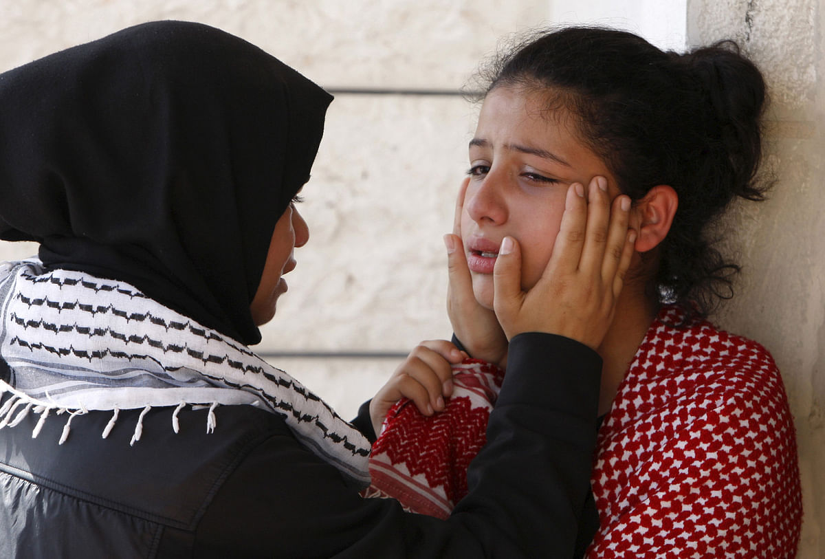 A relative of 27-year-old Palestinian Mutaz Zawahereh, who was killed by Israeli troops during clashes on Tuesday, is comforted as she mourns during his funeral in the West Bank city of Bethlehem (Photo: Reuters)