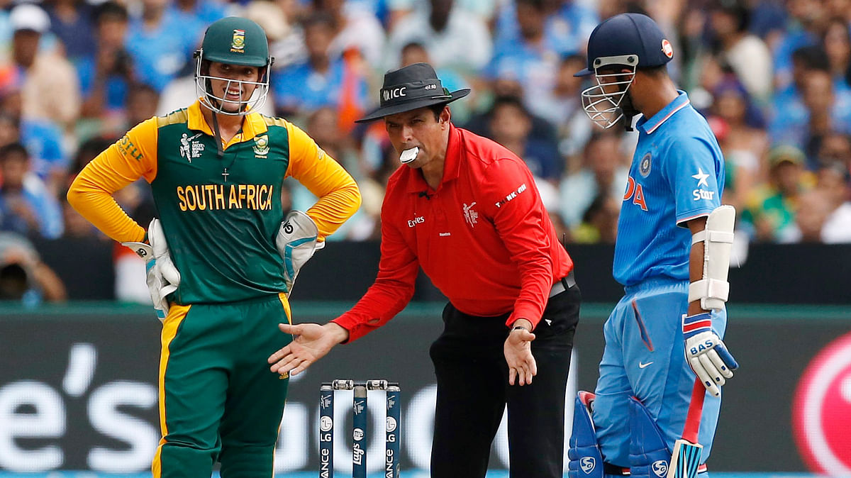 South African wicketkeeper Quinton de Kockas (left) and India's Ajinkya Rahane (right) watch as umpire Aleem Dar sets the stumps during their ICC Cricket World Cup clash. (Photo: Reuters)