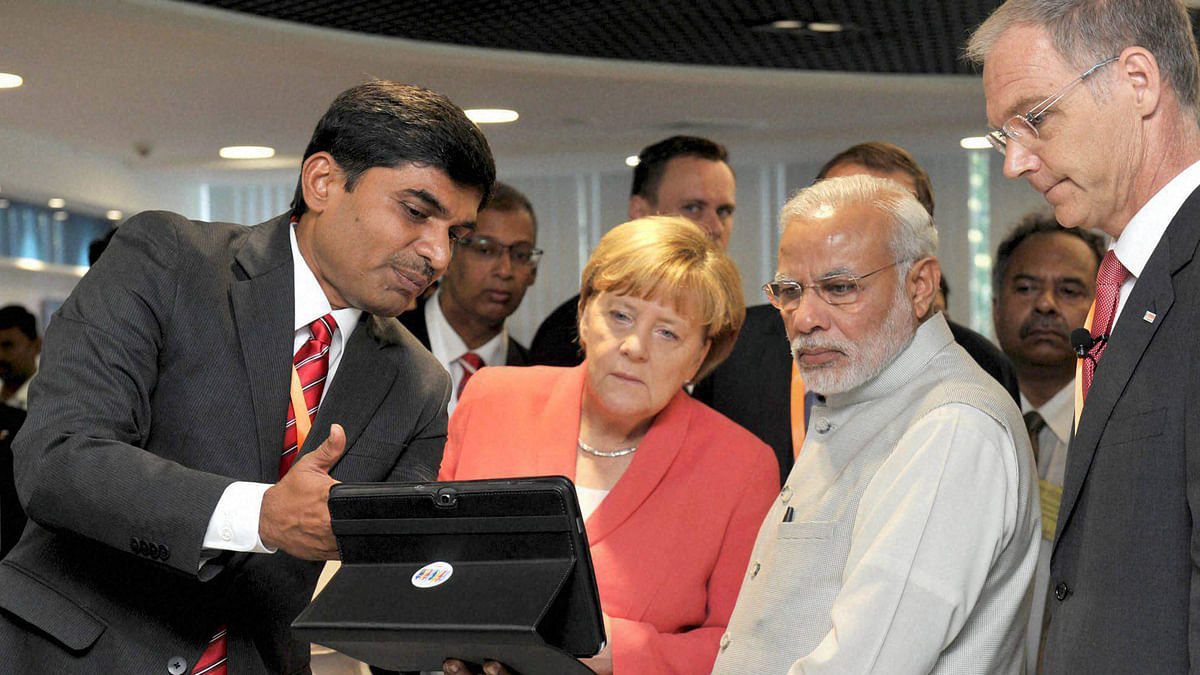 Prime Minister Narendra Modi and German Chancellor Angela Merkel during their visit to Robert Bosch Engineering & Innovation Centre in Bengaluru on Tuesday.(Photo: PTI)