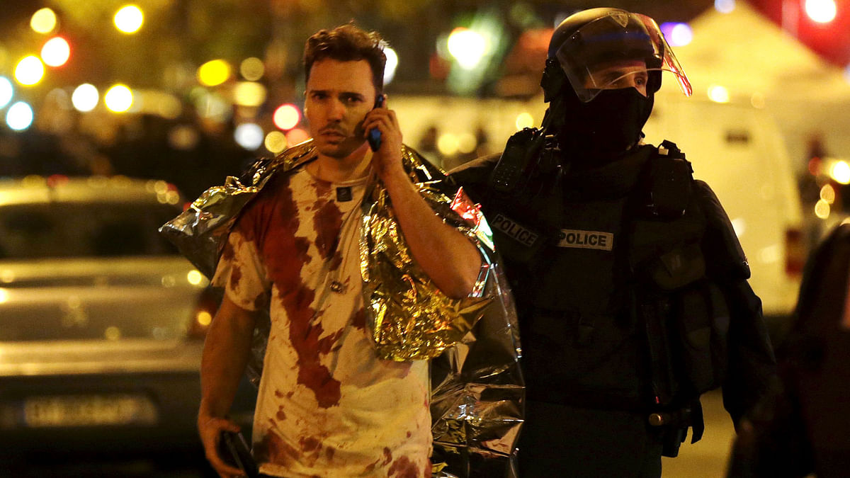A French policeman assists a blood-covered victim near the Bataclan concert hall following attacks in Paris. (Photo: Reuters)