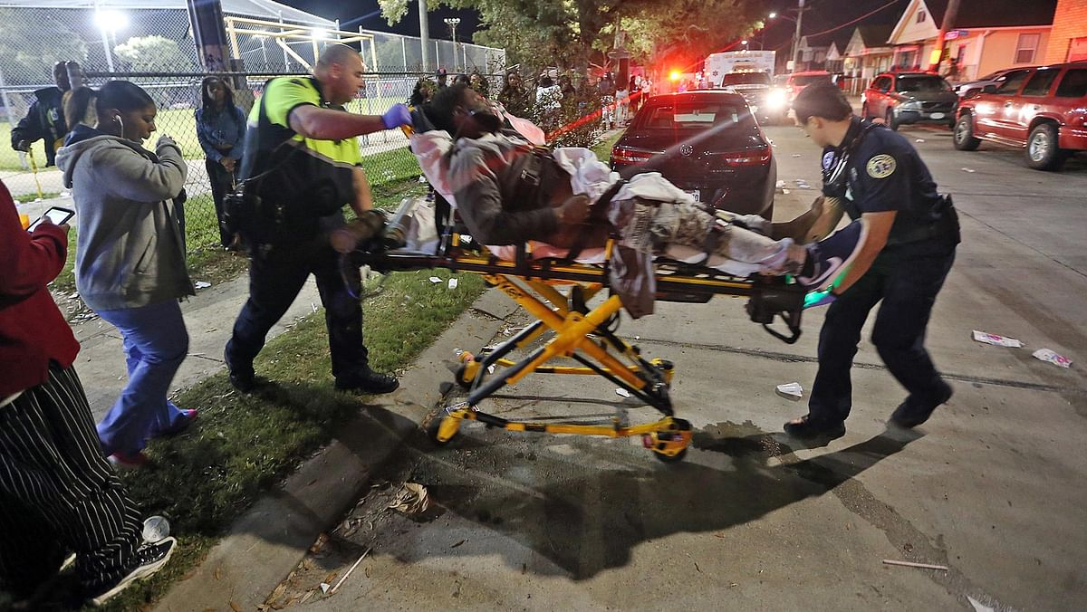 Paramedics carry a person out of the 9th Ward after the shootout. (Photo: AP)