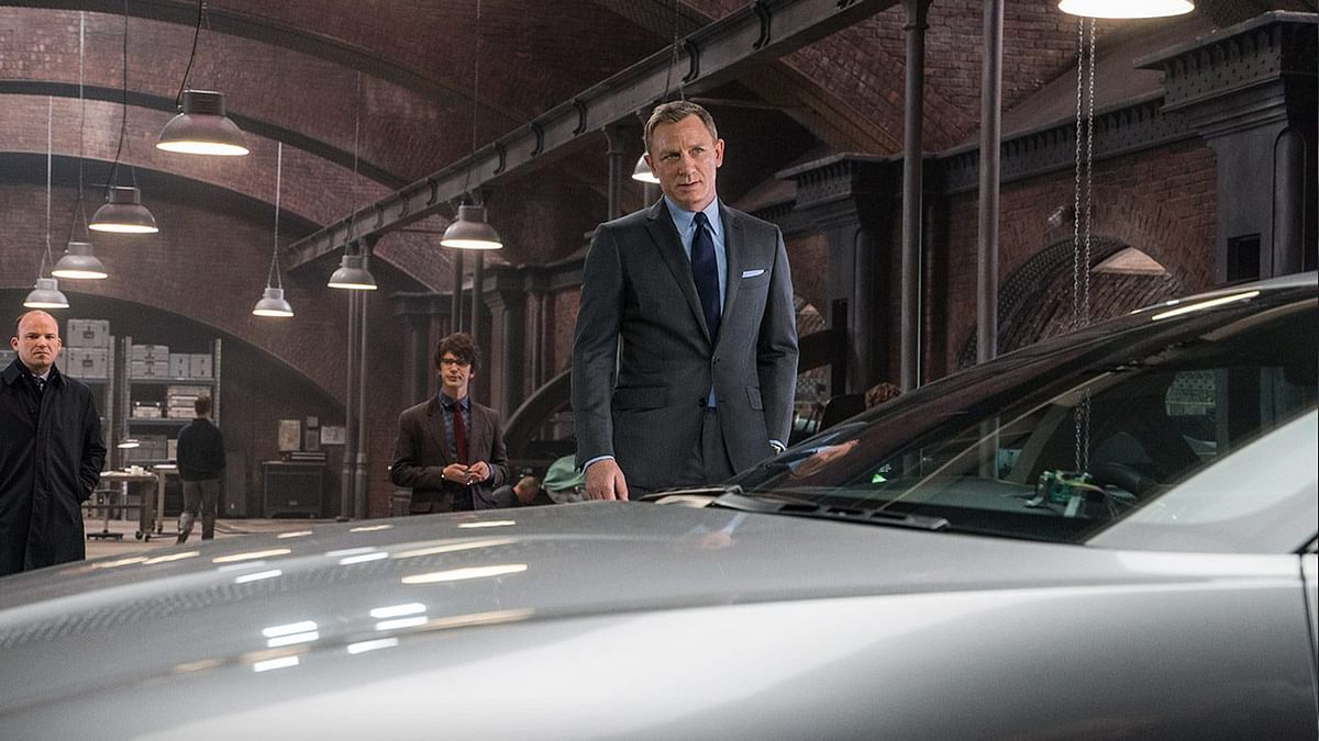 """James Bond (Daniel Craig), Q (Ben Whishaw) and Tanner (Rory Kinnear) with the Aston Martin DB10 in <i>Spectre</i>. (Photo Courtesy: <a href=""""https://www.facebook.com/SpectreMovie/photos/pb.409815059172257.-2207520000.1447991281./482603261893436/?type=3&amp;theater"""">Spectre's Facebook page</a>)"""