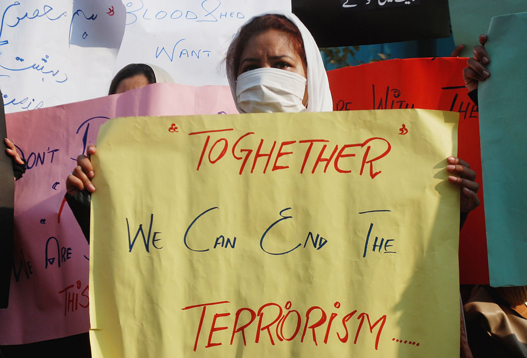 A protester holds a placard in the wake of Peshawar attacks in 2013 in Pakistan. (Photo: Reuters)