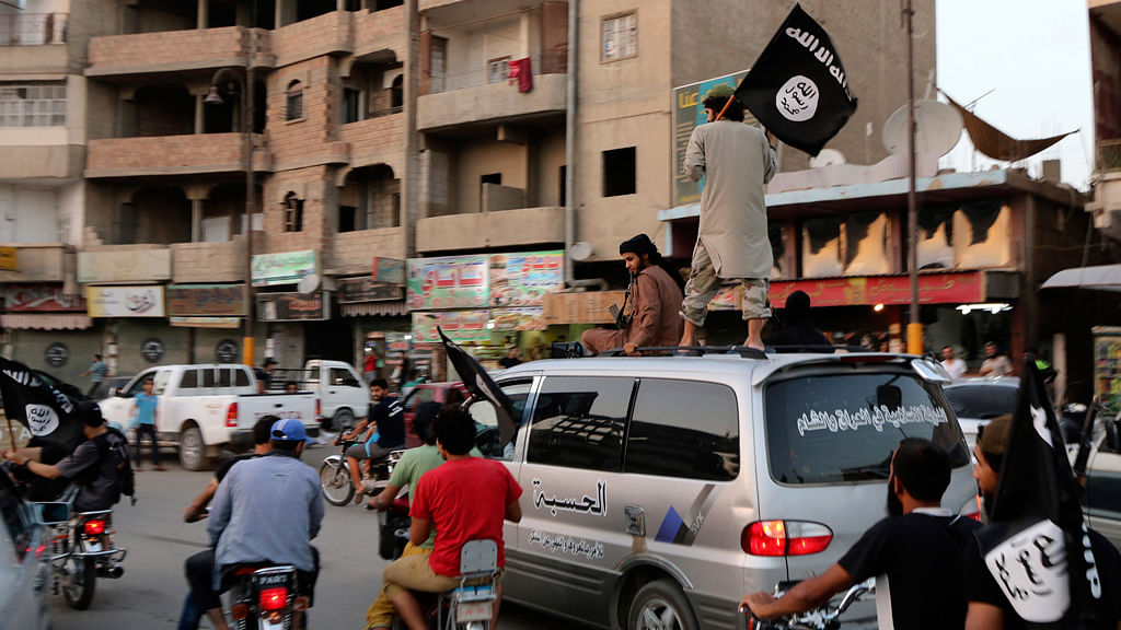 Members loyal to the Islamic State in Iraq and the Levant (ISIS) wave ISIS flags as they drive around Raqqa, Syria (Photo: Reuters)