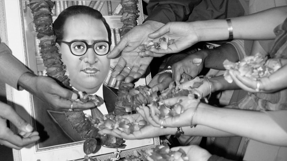 People scatter rose petals in front of a portrait of Dr BR Ambedkar, the author of the Indian Constitution. (Photo: Reuters)