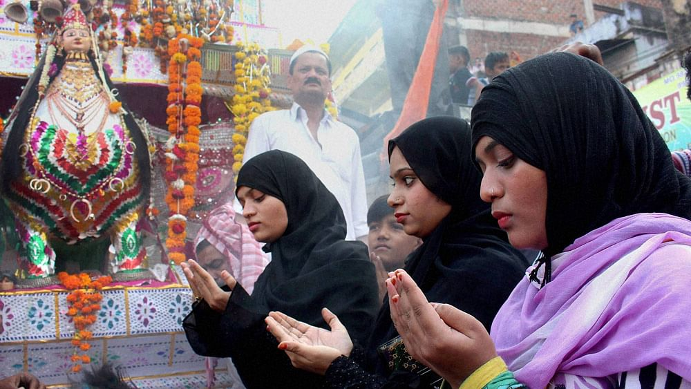 Muslim women  offer prayers in front of a tazia during a Muharram procession in Bhopal. (Photo: PTI)