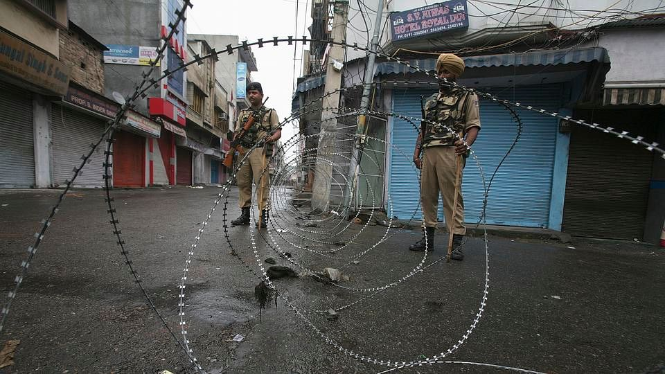 Policemen stand guard on a street in J&K. (Photo: Reuters)