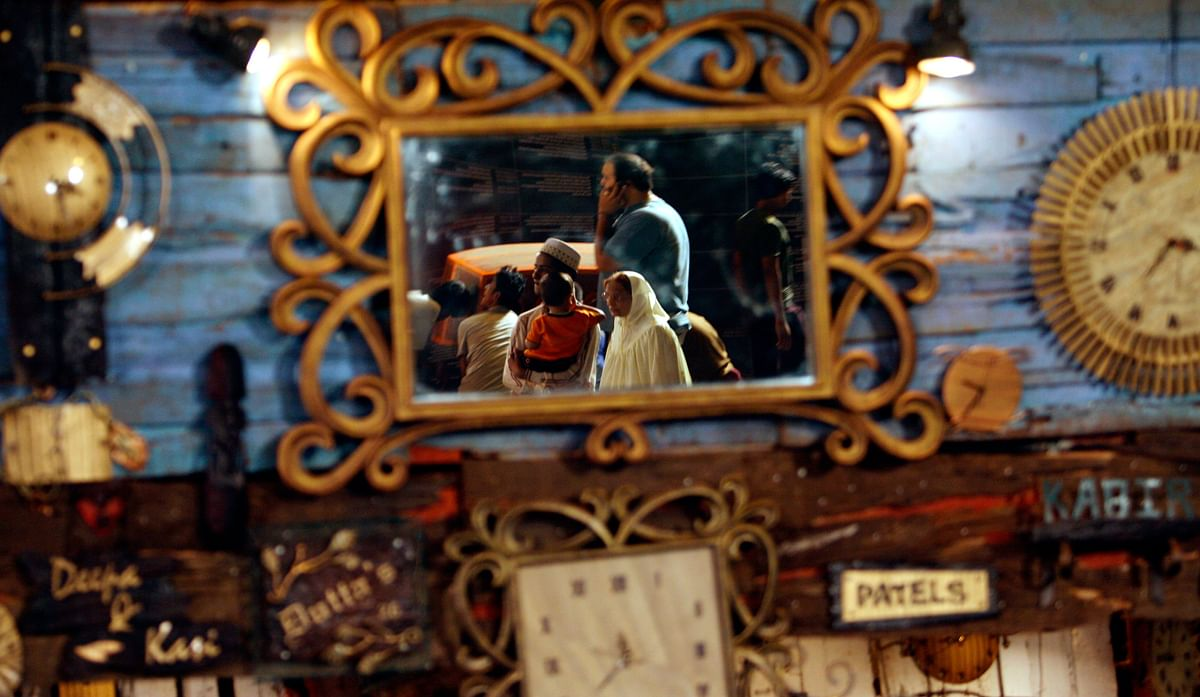 Visitors are reflected in a mirror at a curio shop at the Kala Ghoda arts festival in Mumbai February 13, 2009. (Photo: Reuters)