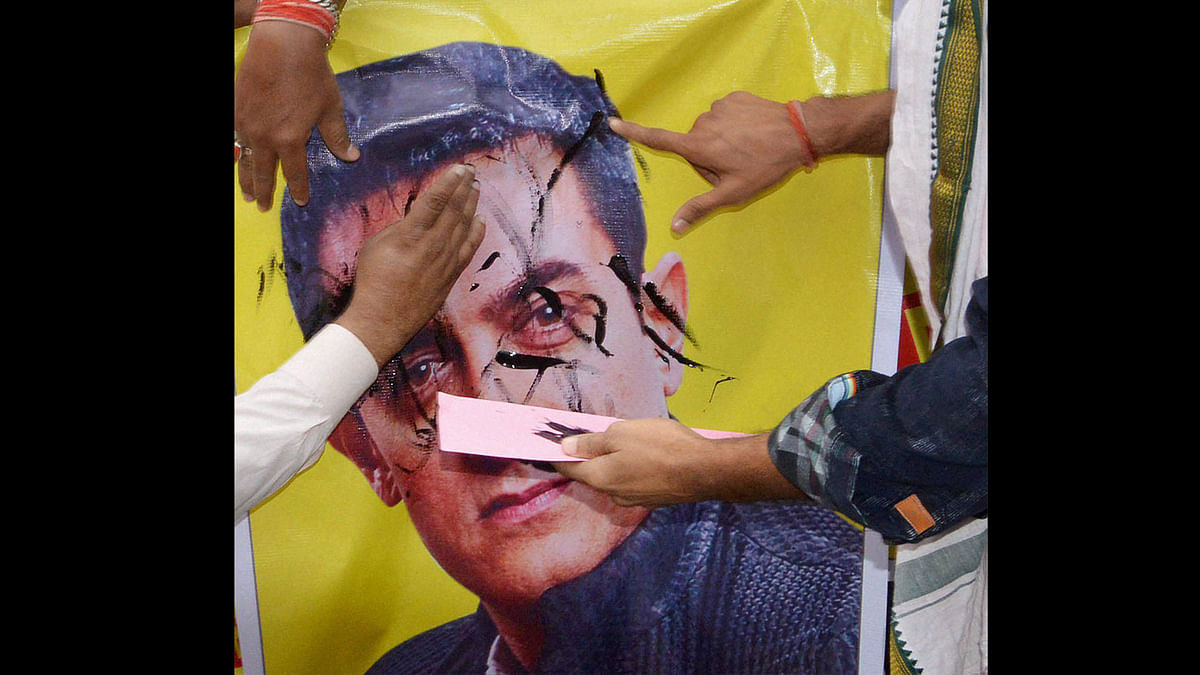 BJP workers putting black ink on a poster of Actor Amir khan during a protest against his statement. (Photo: PTI)