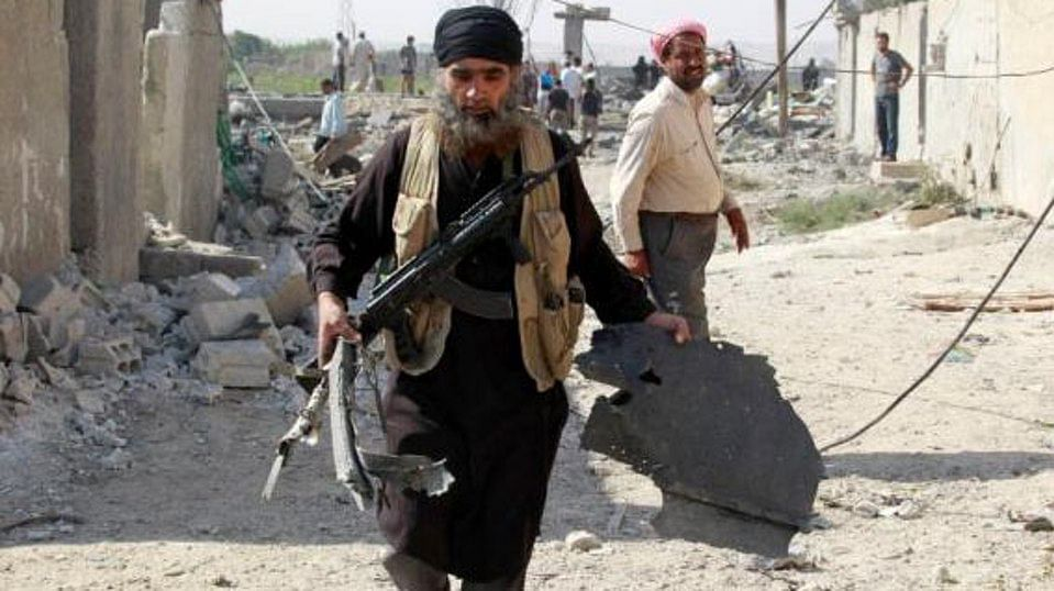 An Islamic State militant carries a piece of wreckage from a Syrian war plane after it crashed in Raqqa, in northeast Syria on September 16, 2014. (Photo: Reuters)