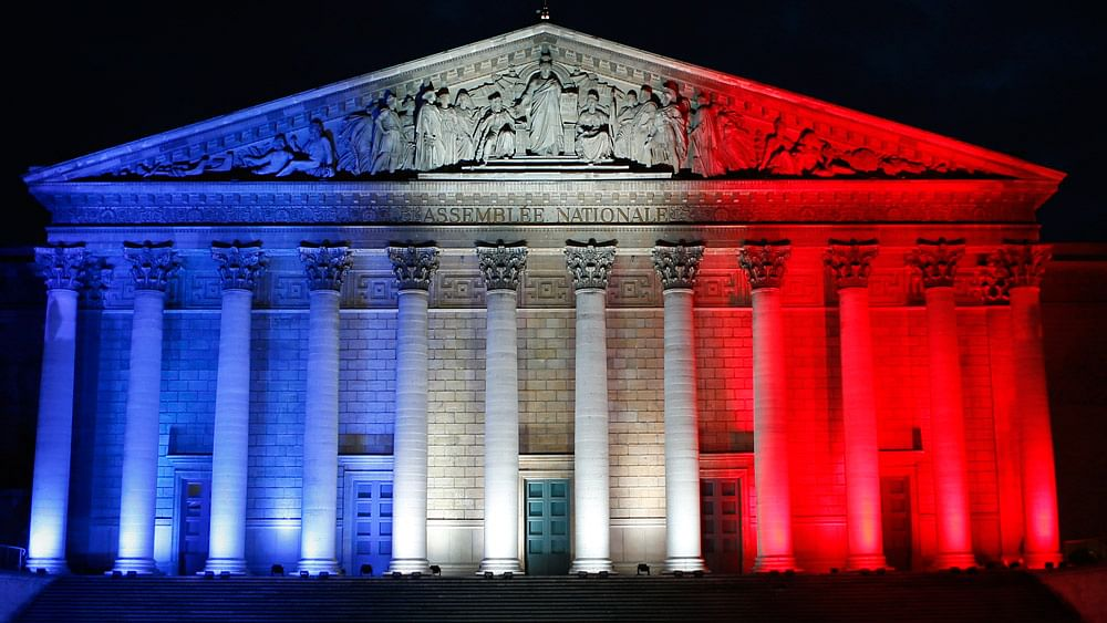 The French Assemblee Nationale, which houses the bicameral Parliament, is lit in the national flag colours, in Paris on November 22, 2015, one week after the Paris attacks. (Photo: AP)