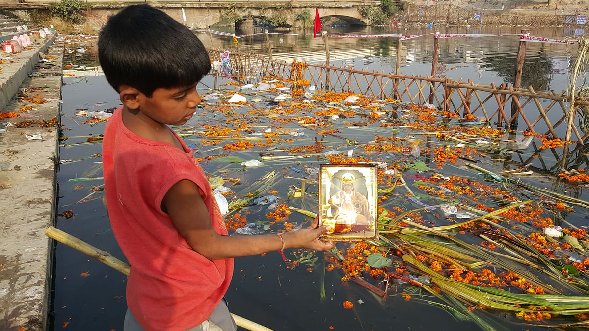 A boy shows a picture frame of Lord Hanuman that he picked from the waters. (Photo: <b>The Quint</b>)