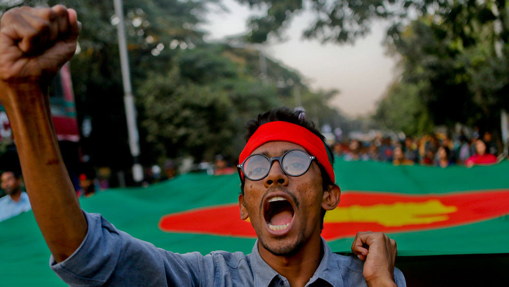 An activist shouts slogans as he holds the side of a huge Bangladeshi flag in a rally, celebrating the execution of two opposition leaders in Dhaka, Bangladesh, November 22, 2015. (Photo: AP)