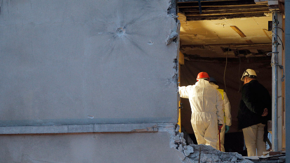 People work inside the damaged building of Wednesday's raid on an apartment in the Paris suburb of Saint-Denis, November 19, 2015. (Photo: AP)