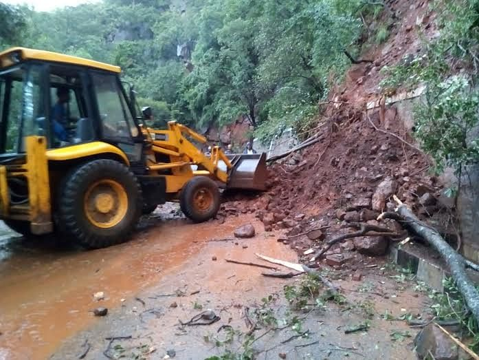 Authorities clear the debris fallen on the ghat road. (Photo Courtesy: The News Minute)