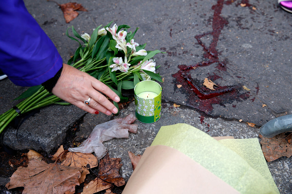 A woman places a candle outside the Bataclan concert hall on Saturday. (Courtesy: AP)
