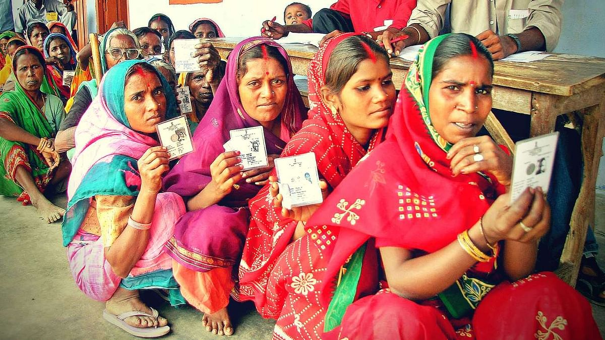 Women hold up their voter ids for a photographer as they wait outside a polling booth in rural Bihar. (Photo: Reuters)