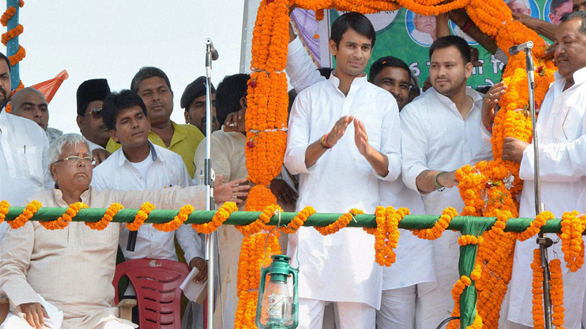 RJD Chief Lalu Yadav with his sons at a rally. (Photo: PTI)