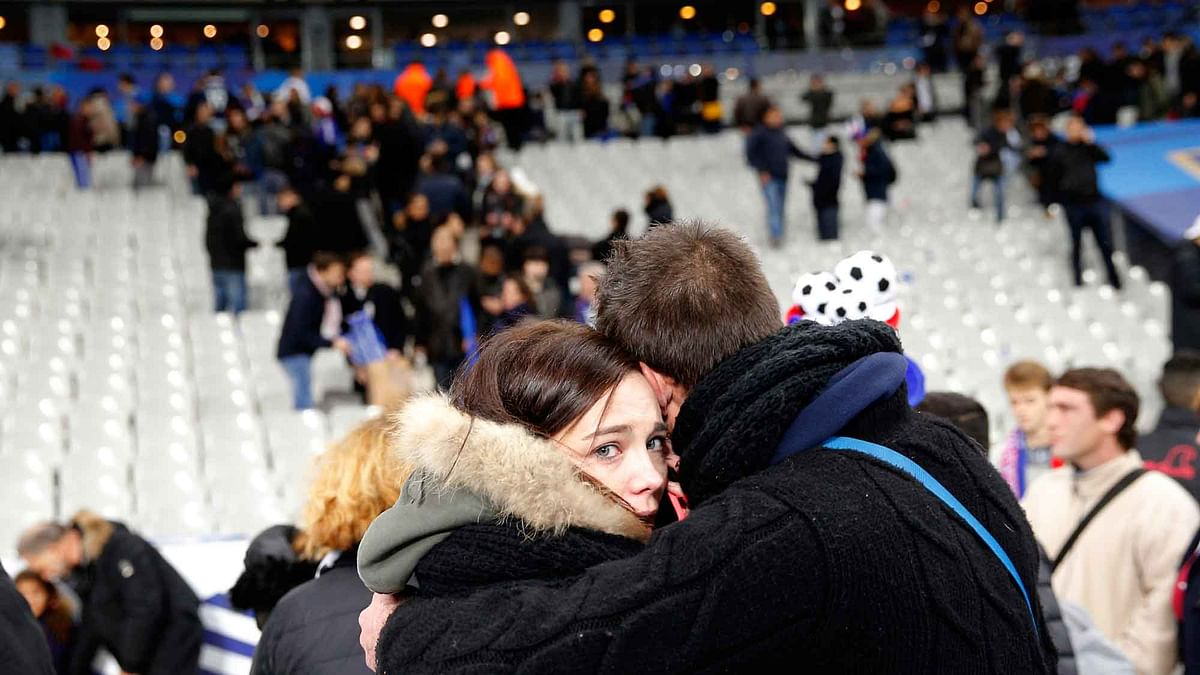 Spectators embrace each other as they stand on the playing field of the Stade de France stadium at the end of a friendly soccer match between France and Germany. (Photo: AP)