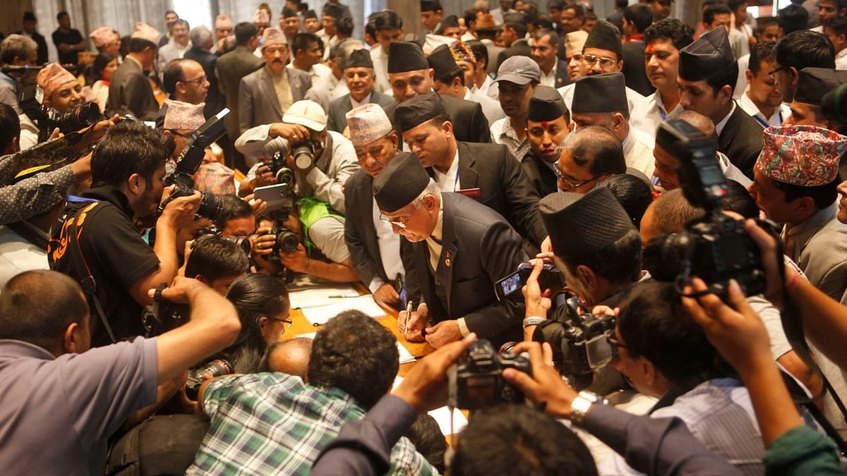 Communist Party of Nepal (Unified Marxist-Leninist) leader KP Oli (Centre) signs the constitution document. (Photo: AP)