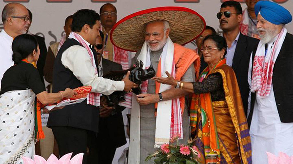 """Narendra Modi wearing a """"Japi"""" (a traditional hat of Assam) receives a wooden Rhino by his supporters during a rally ahead of the 2014 general elections, at Guwahati 2014. (Photo: Reuters)"""