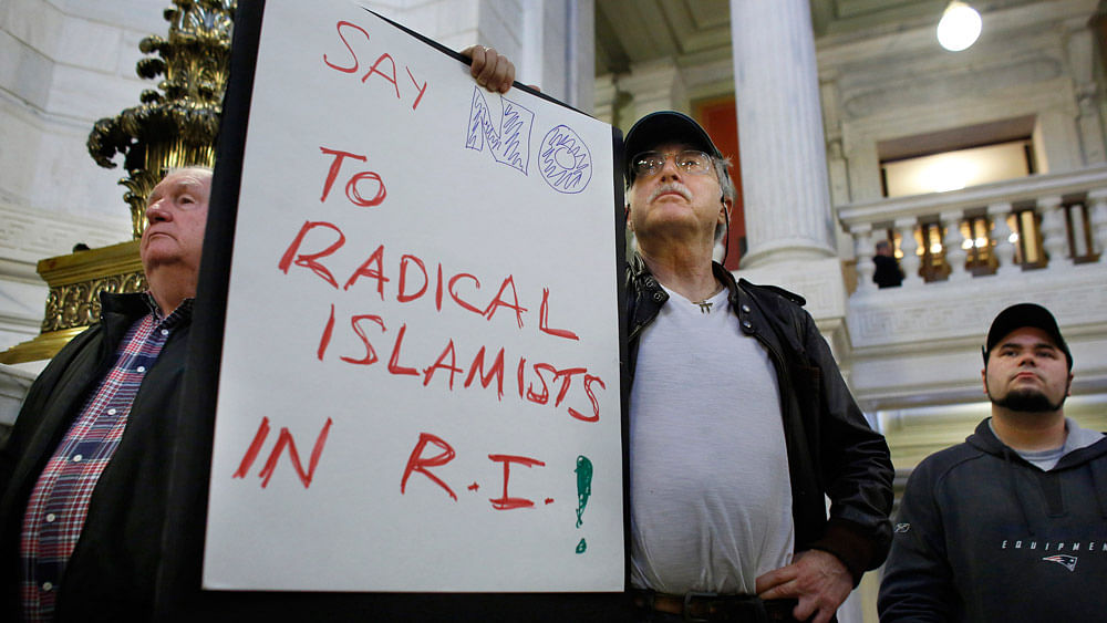 Howard Brown, of North Kingstown, R.I., center, displays a placard during a rally,  November 19, 2015,  held to demonstrate against allowing Syrian refugees to enter Rhode Island following the terror attacks in Paris. (Photo: AP)