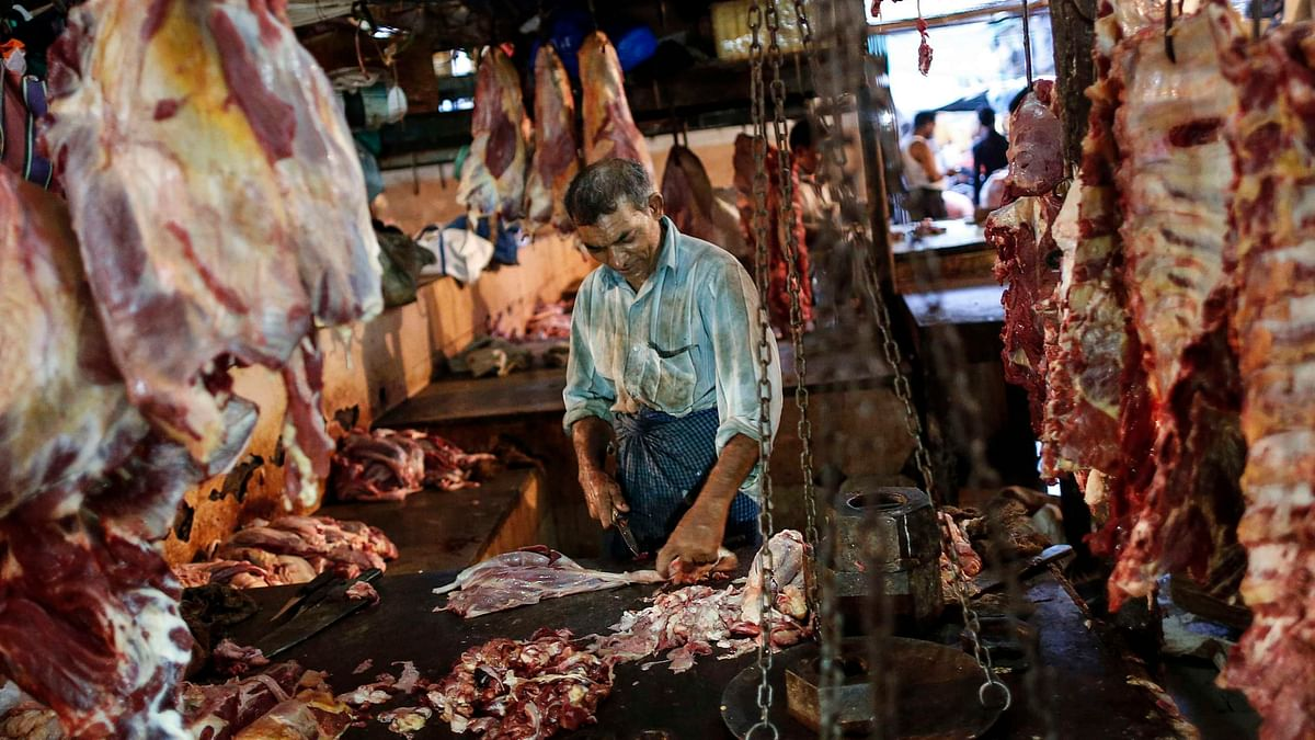 A butcher cuts up portions of beef for sale in an abattoir at a wholesale market in Mumbai.(Photo: Reuters)